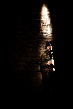 Portrait Of Solider Holding Rifle While Standing By Brick Wall