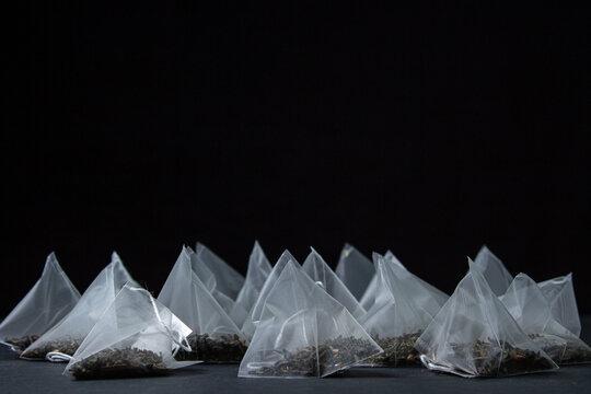 Tea bag pyramid on a black background. Fast brewing tea.