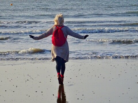 Rear View Of Woman With Arms Outstretched Walking At Beach