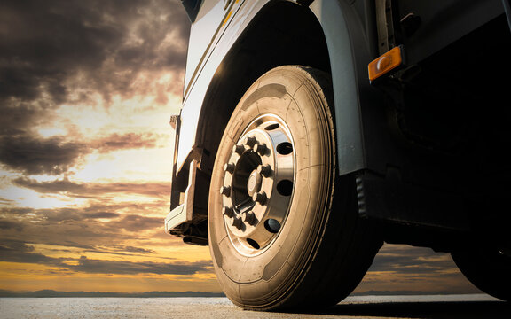 Close-up, Front a big truck wheel, tire of semi truck parked at sunset sky. Industry freight truck transportation.