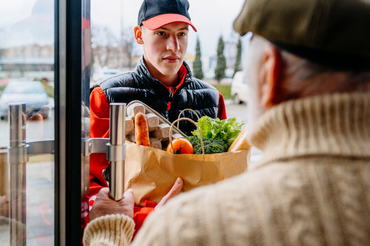 Back view of senior man open door and talking to a food from young delivery man carrying grocery paper bag full of fresh food standing on doorway outdoor.