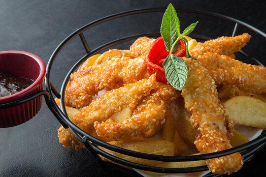 Fried chicken in a metal basket on black background