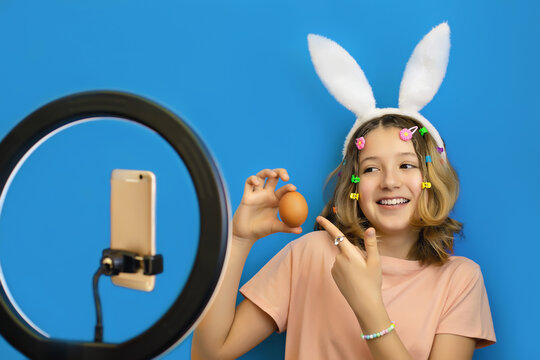 cheerful teenage girl blogger with bunny ears on head holds an egg in her hands and conducts an online broadcast on her smartphone congratulating subscribers in social networks on the Easter holiday