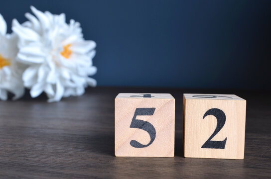 Number 52, rating, award, Empty cover design in natural concept with a number cube and peony flower on wooden table for a background.