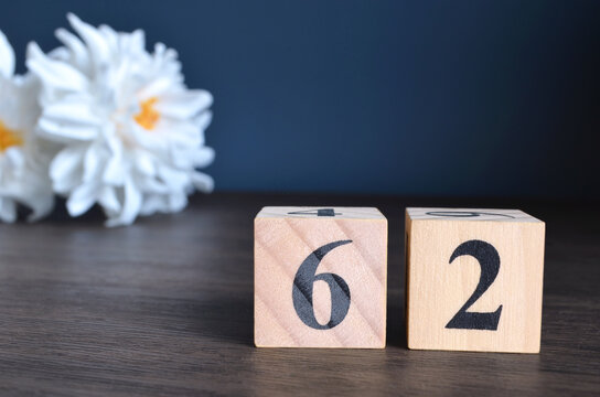 Number 62, rating, award, Empty cover design in natural concept with a number cube and peony flower on wooden table for a background.