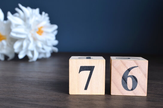 Number 76, rating, award, Empty cover design in natural concept with a number cube and peony flower on wooden table for a background.
