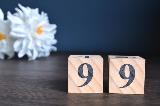 Number 99, rating, award, Empty cover design in natural concept with a number cube and peony flower on wooden table for a background.