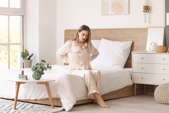 Young woman suffering from back pain in morning because of uncomfortable mattress