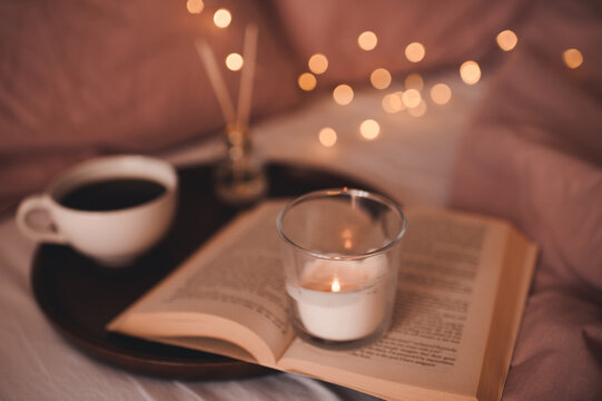 Hygge concept with cup of coffee, open paper book with staying burning candle and glowing lights at background close up. Cozy atmosphere.