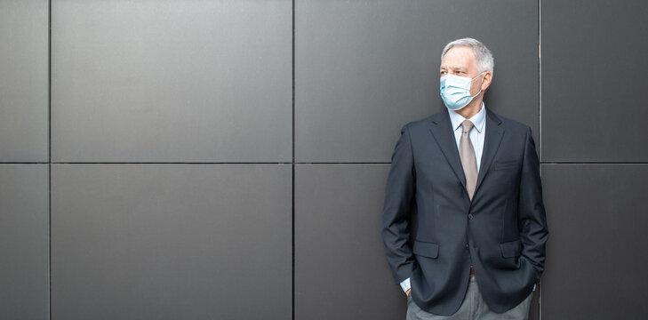Coronavirus covid concept, masked senior businessman standing next to a black wall