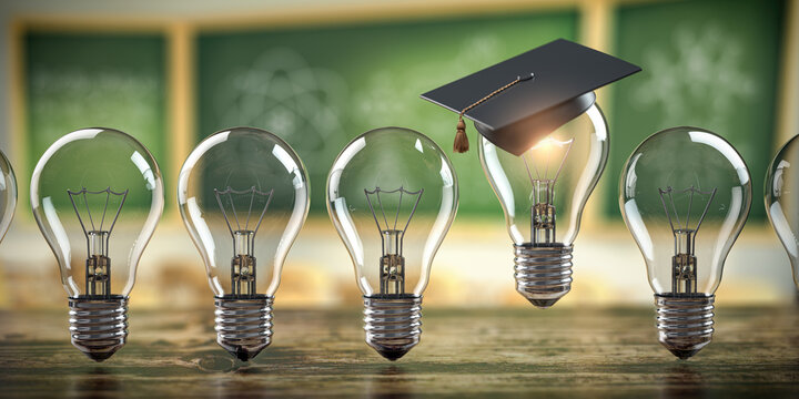 Glowing light bulb with graduation cap in row of other light bulbs on classroom blackboard background. Education, learning on school and university or idea concept.