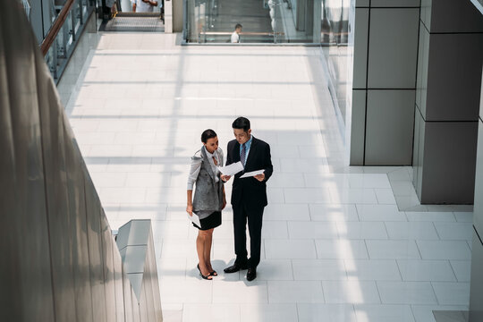 Two business people reading business papers documents. High view of serious businessman and businesswoman standing in office hall and reading upset news