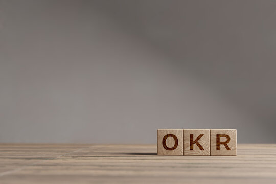 Wood cubes with acronym 'OKR' - 'Objectives and Key Results' on a beautiful wooden table, studio background. Business concept and copy space.
