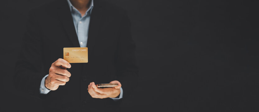 businessman is holding credit card and using mobile phone. Online shopping concept,banking and online shopping at the home.Close up.