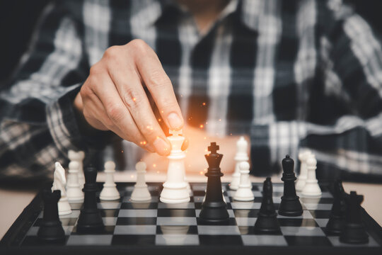 man Analyze chess piece on chess board game concept for ideas and competition and strategy, business success concept, business competition planning teamwork strategic concept.