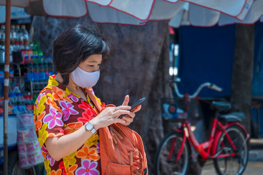 Asian female traveler in colorful casual style with protective mask using smartphone on walkway in seaside area