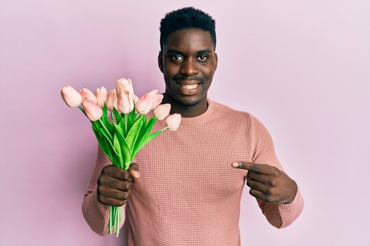 Handsome black man holding bouquet of pink tulips flowers smiling happy pointing with hand and finger