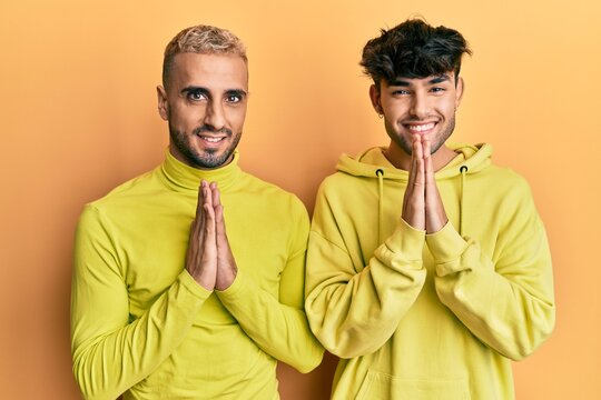 Homosexual gay couple standing together wearing yellow clothes praying with hands together asking for forgiveness smiling confident.