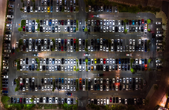 Car traffic, parking and leaving shopping mall's parking lot. Drone aerial top view. Transportation travel, city life, or shopping people lifestyle concept