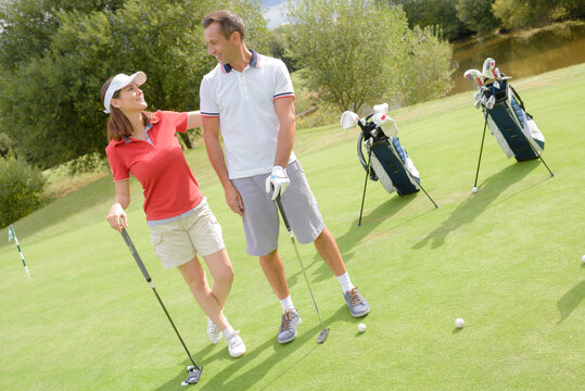 golfing couple conversing on the putting green