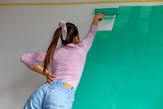 Young happy woman painting an interior wall with a paint roller in a new house.