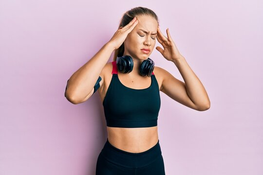 Beautiful young blonde woman wearing gym clothes and using headphones with hand on head, headache because stress. suffering migraine.