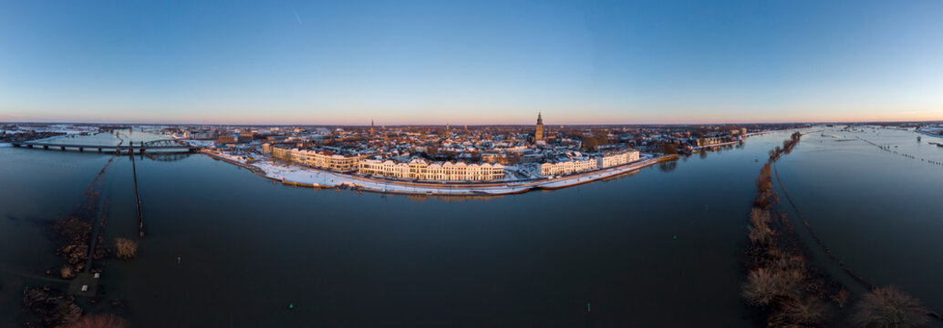 180 degrees sunset aerial panorama of Dutch Hanseatic medieval tower town Zutphen, The Netherlands, with snow on the cityscape boulevard lit up by last daylight with river IJssel in the foreground