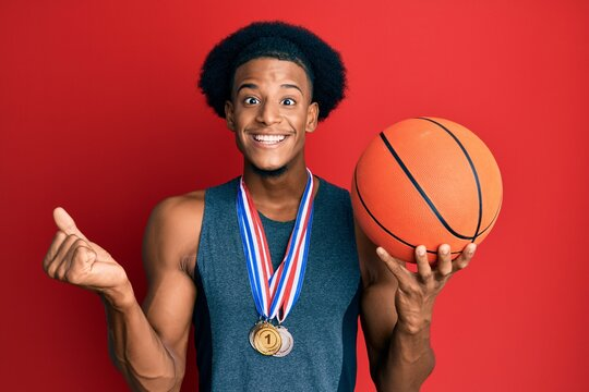 African american man with afro hair wearing winner medals at basketball player screaming proud, celebrating victory and success very excited with raised arm