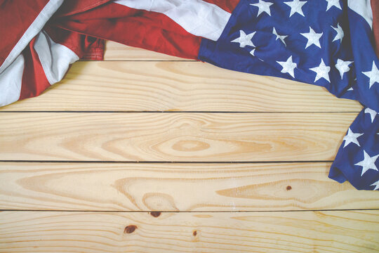 Close up of waving national usa american flag on woodenbackground.