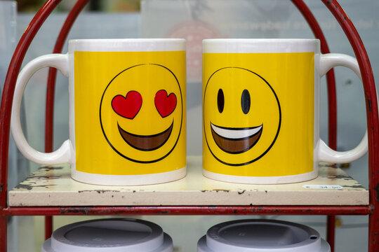 Gelbe Smiley-Tassen mit verliebtem Herz-Smiley und lachendem Smiley