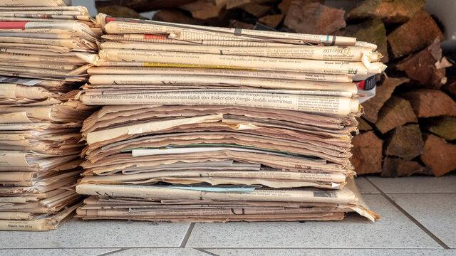 Ein stapel mit Altpapier aus alten Zeitungen vor einem Holzstapel