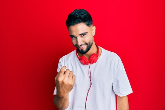Young man with beard listening to music using headphones beckoning come here gesture with hand inviting welcoming happy and smiling