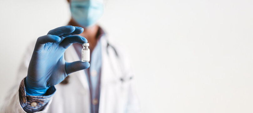 Selective focus in a glass jar in the hands of a doctor wearing gloves