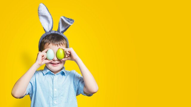 Happy child wearing bunny ears and holding colorful easter eggs in front of his eyes on a yellow background. Happy boy in easter bunny costume with easter eggs