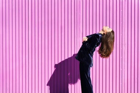Woman wearing blue suit posing near pink shutter.