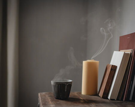 Dampfende Teetasse und gelöschte Kerze