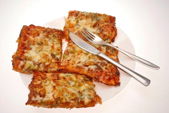 Pizza auf Teller mit Messer und Gabel