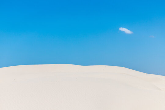 Dunes with sand an small cloud in blue sky