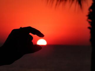 Fototapeta Optical Illusion Of Person Holding Sun Against Sky During Sunset