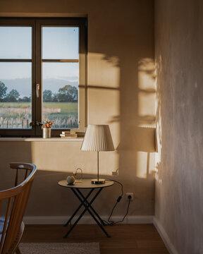 Sonnenschein in einem Wohnraum mit Sicht aus dem Fenster dahinter Felder