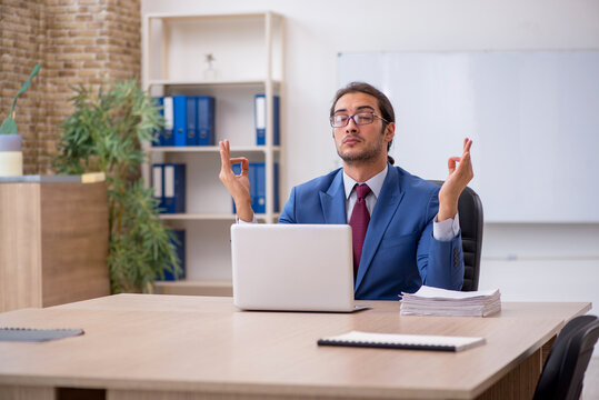 Young male employee sitting in the office in front of whiteboard