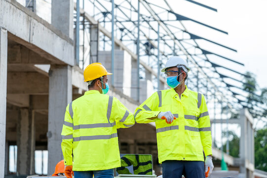 Construction Worker greeting with elbows while wearing protectiv