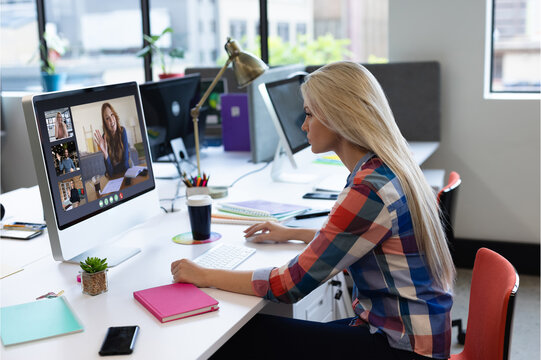 Caucasian woman in office having video call with diverse colleagues displayed on computer screen