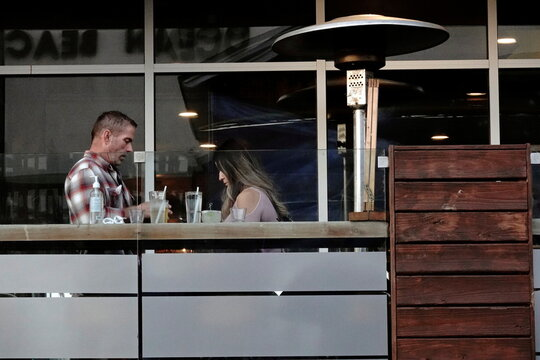 A couple dines outdoors next to a space heater at a restaurant in San Diego