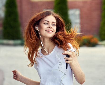 redhead woman outdoors walk headphones fun music