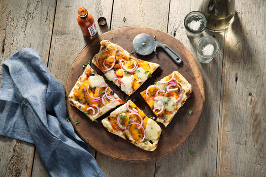 Overhead view of pizza slices on cutting board on table