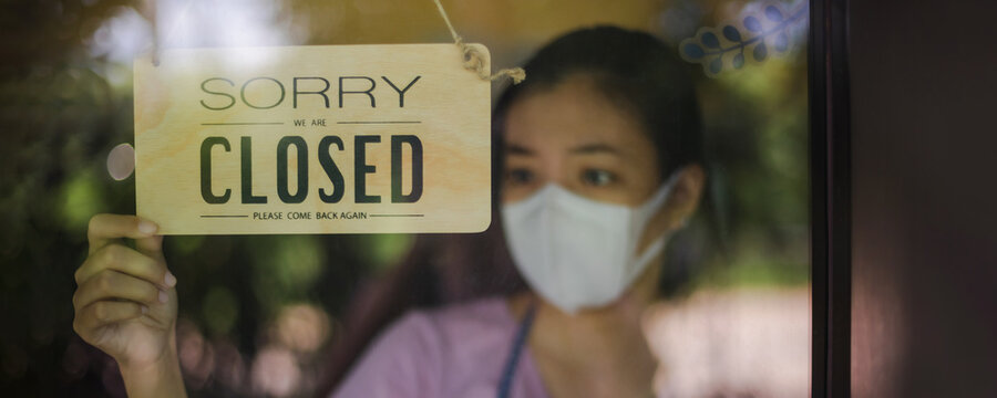 Close up shot of woman wearing mask and hand turning closed sign board on glass door in coffee shop and restaurant after covid-19 lockdown quarantine.Business crisis concept.