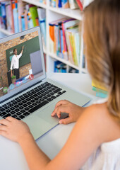 Female student having a video call with male teacher on laptop at library