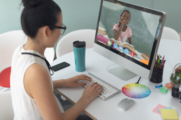 Female teacher having a videocall with female student on computer at home