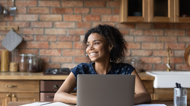Close up smiling dreamy African American woman distracted from laptop, looking to aside, dreaming about new opportunities, visualizing future, pondering strategy, working or studying online at home